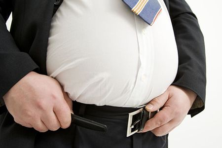 толстый мужчина застегивает пояс