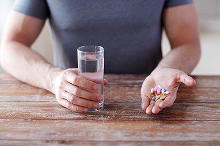 таблетки и стакан воды в руках у мужчины