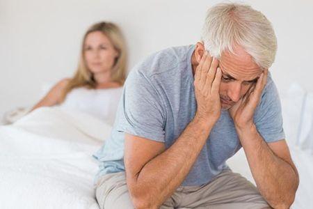 пожилой мужчина грустит сидя на кровати