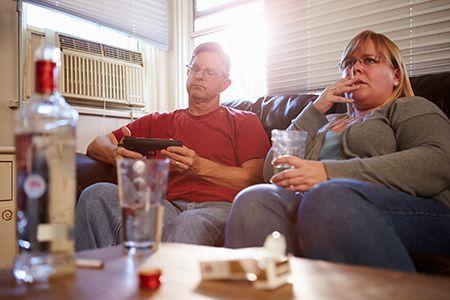 мужчина и женщина сидят на диване перед алкоголем